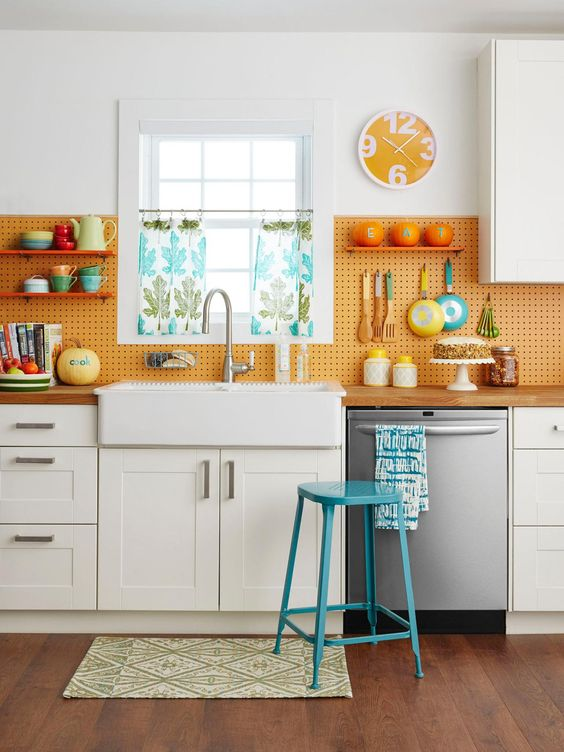 kitchen with wooden floor, white cabinet, brown wooden top, white sink, white wall, orange pegboard