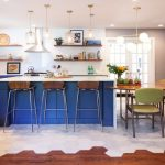 Kitchen With Wooden Floor, White Tiles, Blue Wooden Island With White Top, Half Round Dining Table With Wooden Chairs, Hanging Lamps