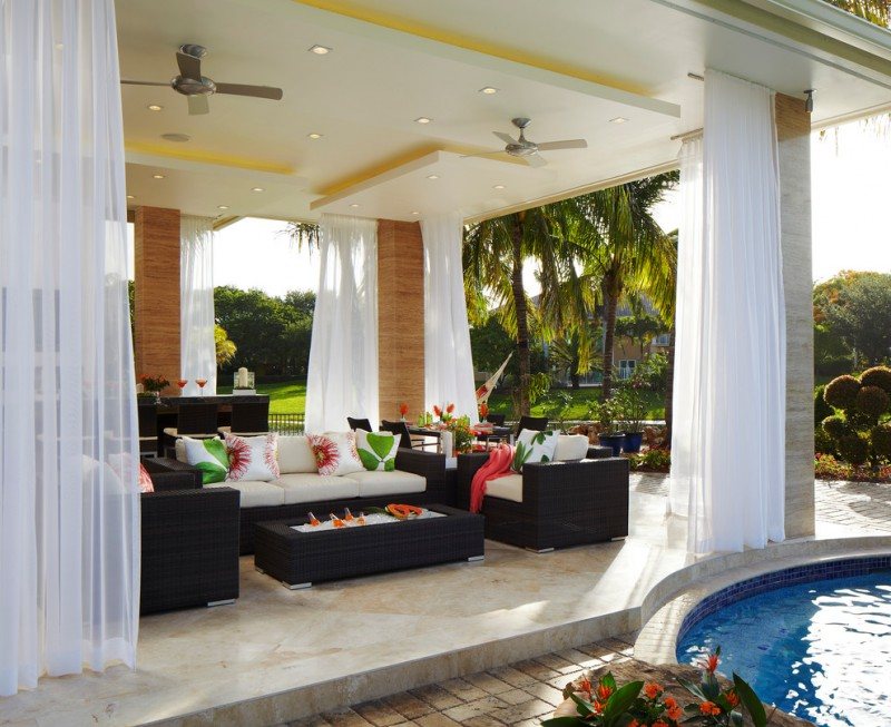 lanai under a white ceiling, marmer floor, black rattan sofas, black rattan coffee table