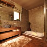 Large Bathroom With Brown Nuance, Brown Floor, Brown Marble Wall, Brown Wooden Floor In Shower Part, Brown Wooden Cabinet, White Lowered Tub With White Stones On Two Sides