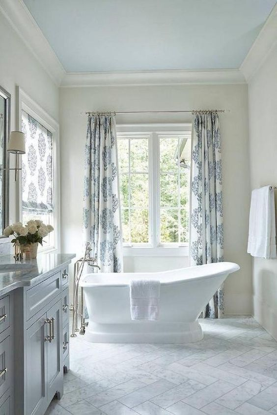 light grey bathroom with light grey flooring, white wal, white tub, light grey cabinet and sink, white sconces