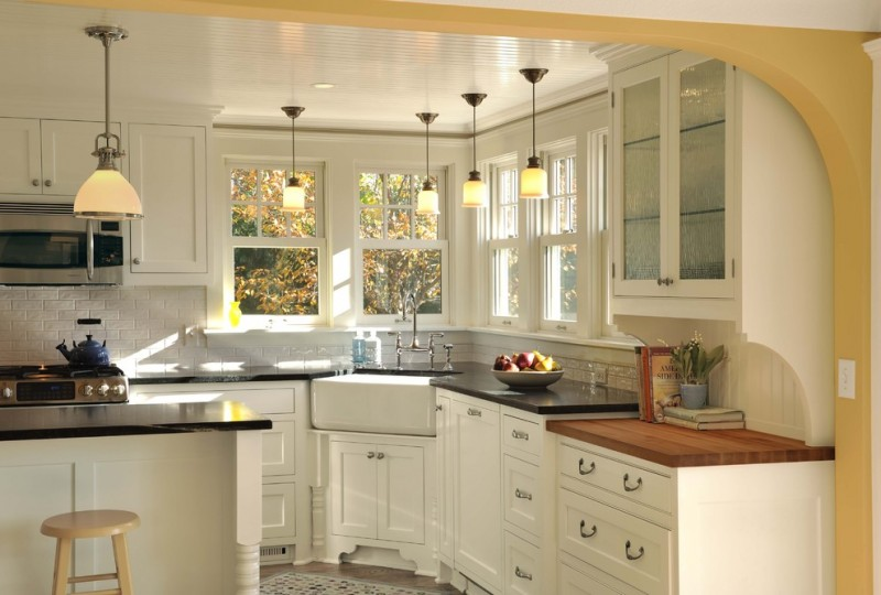 light over kitchen sink black countertop white island white cabinets stove microwave frosted glass front door subway backsplash