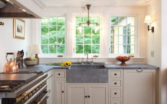 light over kitchen sink grey countertop windows range hood stove oven kettle wall sconce kitchen cabinets faucet dishwasher