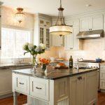 Light Over Kitchen Sink Grey Kitchen Cabinets Grey Island Chandelier Black Marble Countertop Window Stovetop Range Hood Wooden Floor