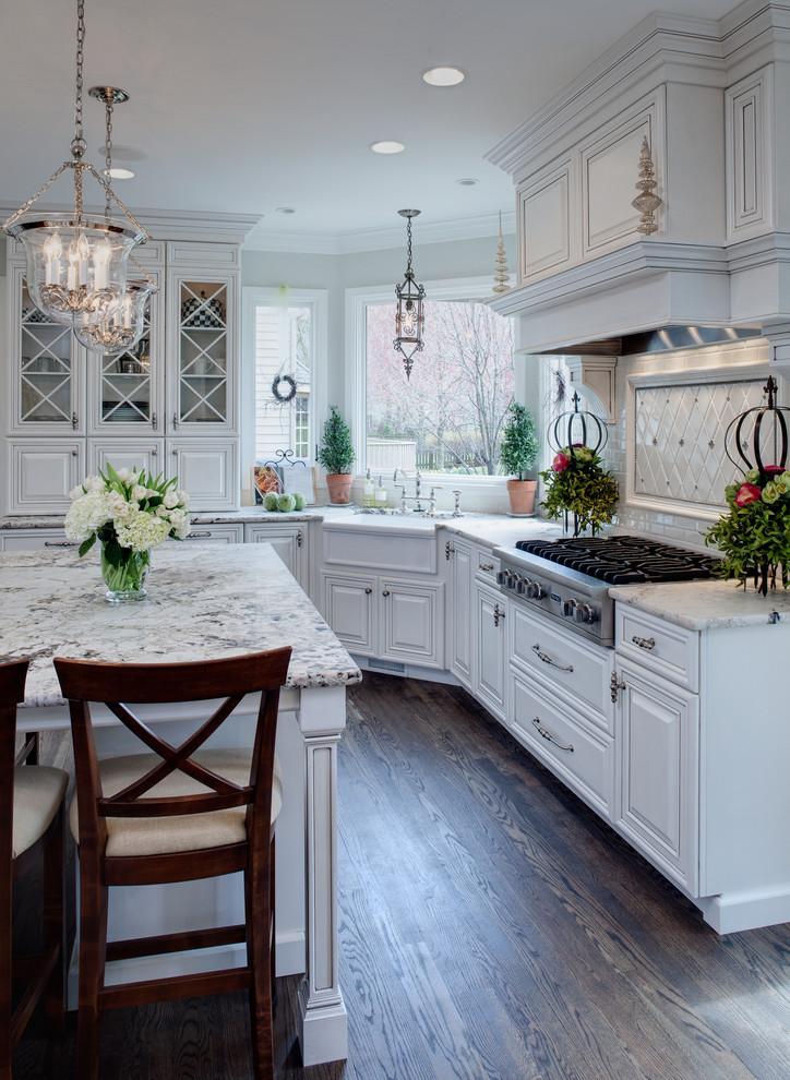 light over kitchen sink white cabinets white island wooden barstools wooden floor backsplash windows white granite countertops stove range hood