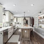 Light Over Kitchen Sink Wooden Island Chevron Kitchen Mat Wooden Floor White Cabinets Built In Shelves Wall Sconces Stove Oven Dishwasher