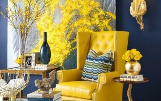 living area with blue painted wall, yellow chair, metallic coffee table, wooden side table, wooden coffee table, fire like sconce, painting