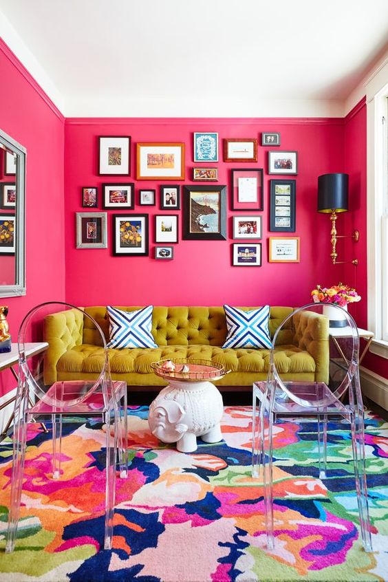 living room pink wall, yellow sofa, glass chairs, white elephant statue coffee table, wide mirror, blue sconce, paintings