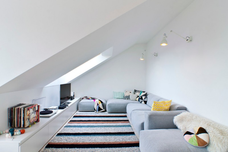 living room under slanted roof, striped rug, grey sofas, TV on white long low cabinet, pendant