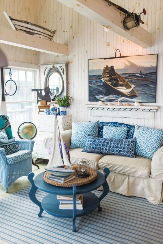 living room with blue striped rug, beige sofa, blue pillows, blue rattan chair, white wooden wall, wooden beams, blue coffee table, paintings