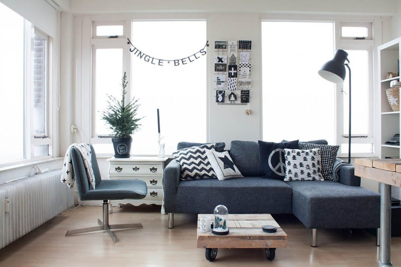 living room with brown wooden floor, white walls, white cabinet, white wooden shelves, dark blue sofa and chair, black floor lamp