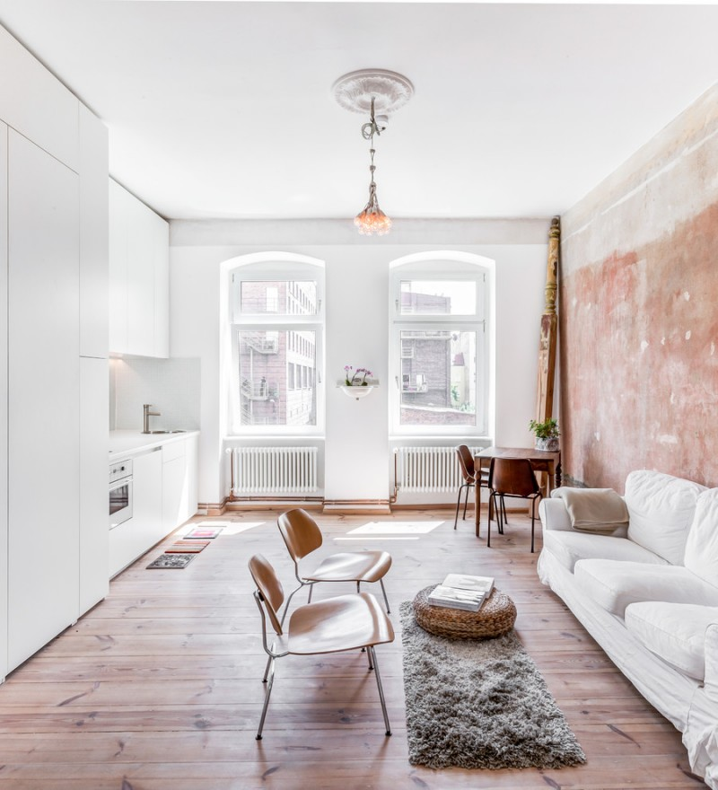 living room with brown wooden flooring, white wall with one side in soft red wallpaper, short chandelier, white sofa, wooden chairs, grey rug with rattan ottoman