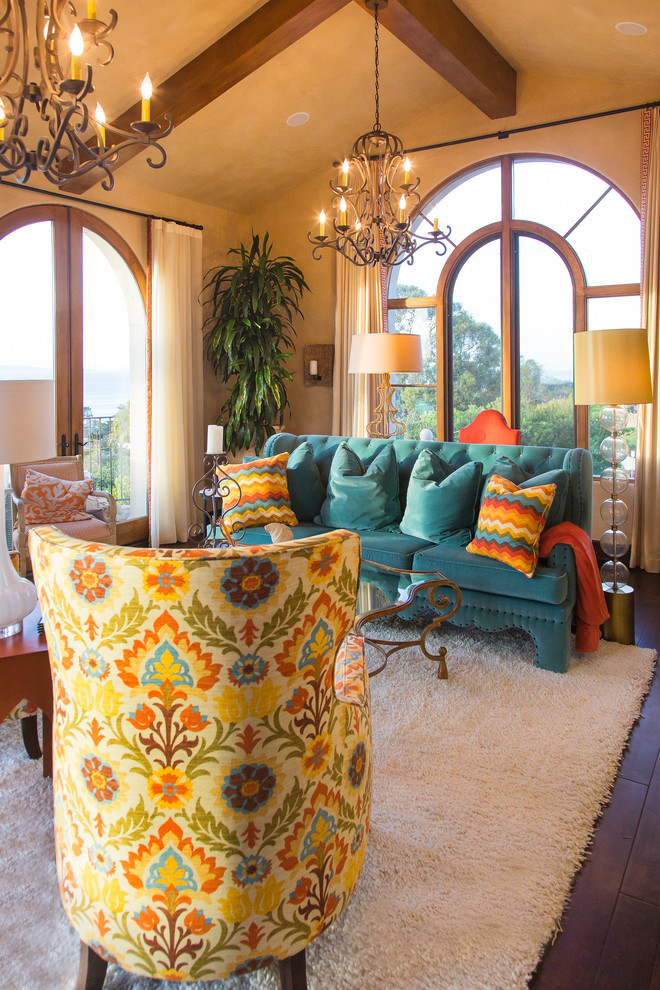 living room with dark wooden flooring, white rug, turquoise couch, with colorful pillow, patterned couch, wooden table, chandelier, warm brown wall and roof
