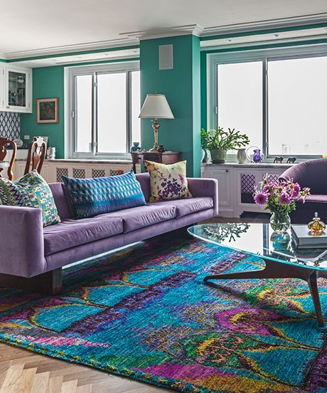 living room with green wall, colorful rug, purple sofa, wooden coffee table with glass top, white table lamp, white cabinet
