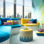 Living Room With Grey Granite Floor, Blue And Yellow Cushioned Sofa, Yellow And Blue Ottoman For Table, Blue Wall, Blue Painted Wooden Shelves