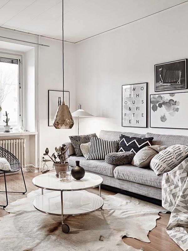 living room with grey sofa, grey pillows, metallic white round coffee table, metallic hanging lamp, white wall, wooden flooring