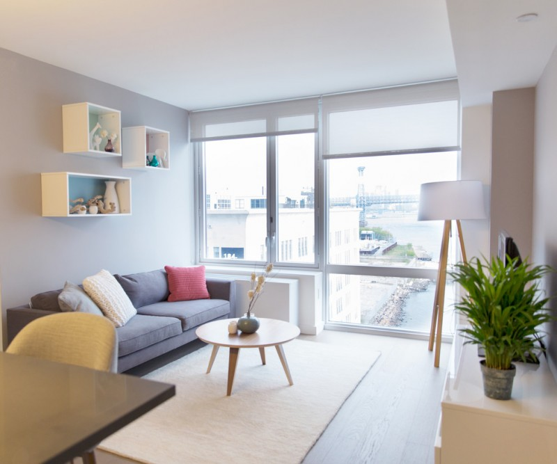 living room with grey wooden floor, brown rug, grey sofa, soft beige char, white wooden hanging shelves, white floor table, light brown cabinet