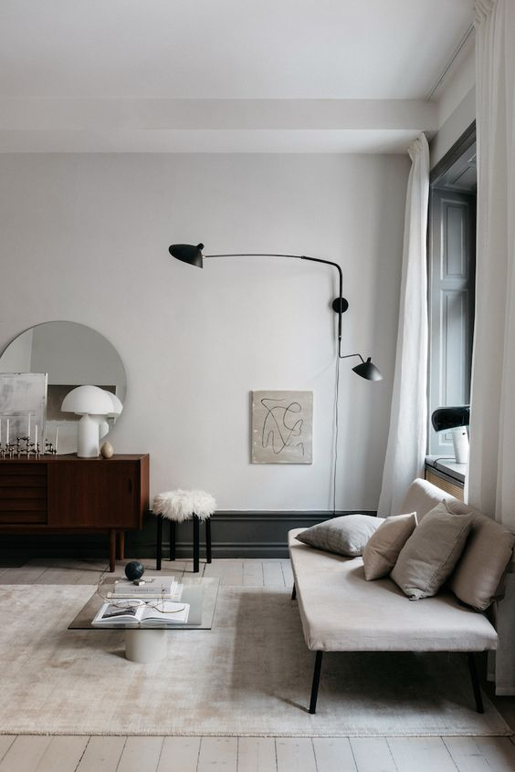 living room with ligiht wooden flooring, brown cabinet with round wide mirror, white fur stool, white rug, black metallic wall lamp, nude bench with metallic feet