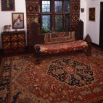 Living Room With Mediterranean Rug, Red Brown Ethnic Patterned Curtain, Brown Wooden Bench Red Brown Patterned Cushion, Brown Wooden Cupboard