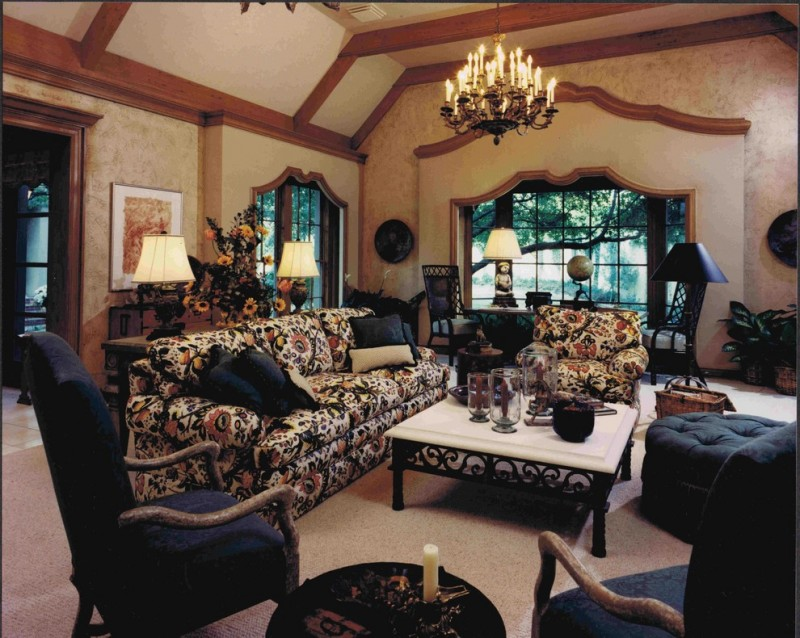living room with nude rug,  flower pattern brown couch, blue couches, blue ottoman, black coffee table with white marble top, light brown wall and ceiling wi
