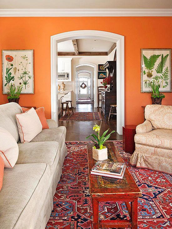 living room with orange wall, grey sofa, wooden long coffee table, Persian rug