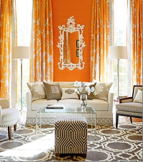 living room with orange wall, orange curtain, white sofas, clear glass table, mirror, white floor lamp, black and white ottoman