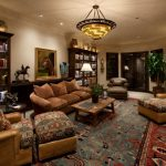 Living Room With Persian Rug, Brown Couch, Brown Long Couch With Ottoman, Wooden Coffee Table, Light Brown Wall And Ceiling With Ceiling Lamp, Dark Brown Boo