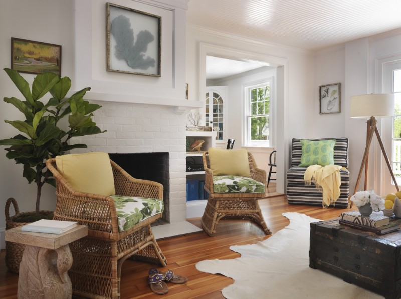 living room with rattan chair with plants patterned cushion, wooden flooring, black wooden chest for table, striped couch