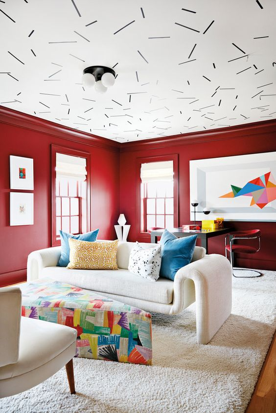 living room with red wall, white ceiling, wooden floor with white rug, white sofas, colorful pizza ottoman as coffee table, black table with red chairs