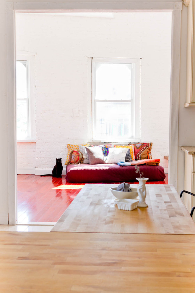 living room with red wooden floor, red low sofa, white painted wall, white cabinet