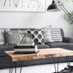 Living Room With White Rug, Wooden Coffee Table, Dark Grey Sofa With Black And White Pillows, Black Metallic Floor Lamp