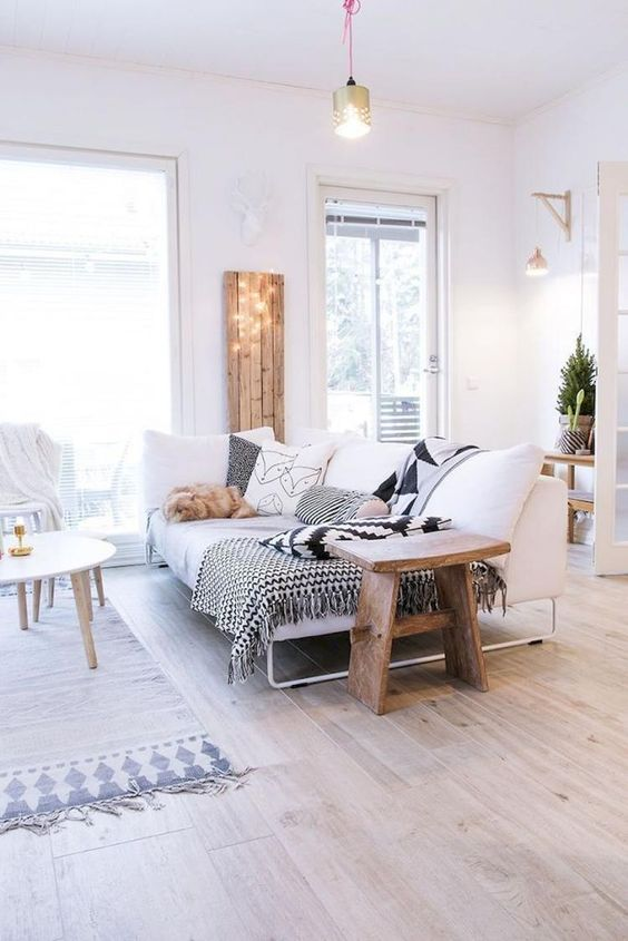 living room with white sofa lounge, wooden side table, white wooden coffee table, rug, light brown wooden flooring, pillows in black and white, wide glass window