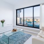 Living Room With White Wall, Floor, White Wooden Cabinet, White Sofa, White Curtain, Clear Glass Coffee Table, Blue Fur Rug