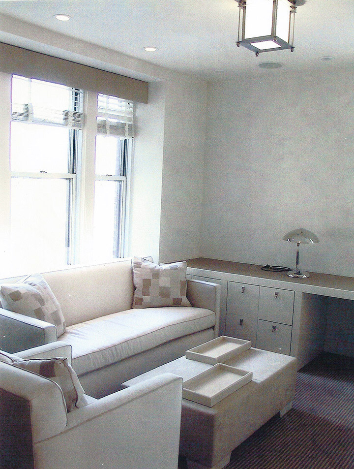 living room with white wall, thin stripped rug, white coffee table, white cabinet, silver metal table lamp, pendant on the ceiling
