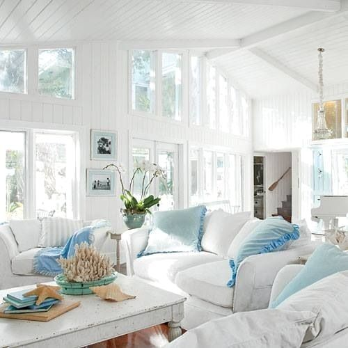 living room with white wall, white sofas, blue pillows, white coffee table, brown wooden floor, white wooden vaulted ceiling