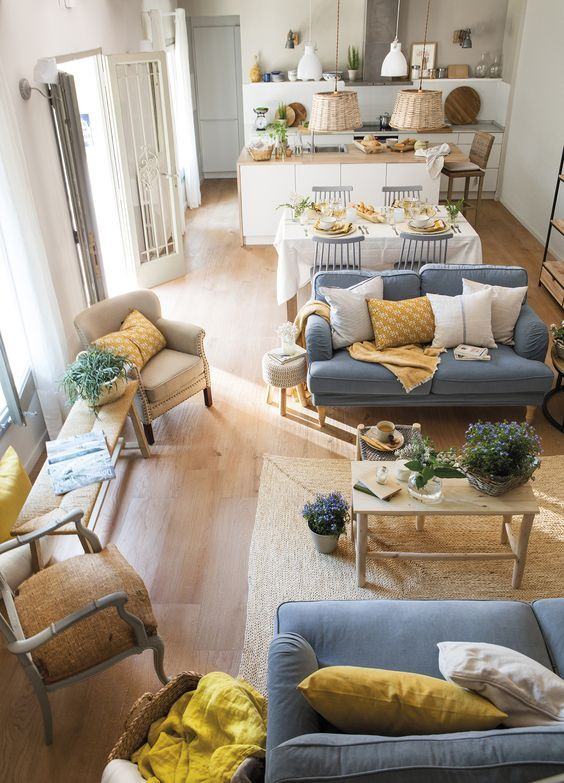 living room with wooden floor, tall doors, wide windows, white wall, blue sofas, brown chairs, wooden coffee table