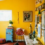 Living Room With Yellow Paitned Wall, Wooden Floor, Wooden Cabinet, Blue Cabinet, Paitings