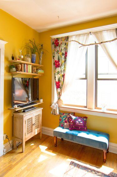 living room with yellow wall, yellow wooden floor, blue small bench, wooden cabinet under a TV and wooden shelves, flowery curtain