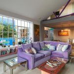 Living Roomwith Beige Wall, Beige Flooring, Purple Sofa, Long Low Bookshelves, Red Coffee Table, Glass Side Tables