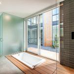 Long Bathroom With Grey Linoleum Flooring, Some Part Wooden Floor With Sunken White Bathtub Near The Glass Sliding Door