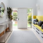 Long Hallway With White Marble Floor With Monochrome Rug, White Shoes Storage Under Yellow Cushioned Bench, Metallic Table With Grey Marble Top, Metallic Framed Round Mirror