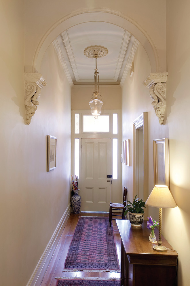 long hallways with woden floor and rug, white wall, wooden cabinet with lamp, wooden chairs, white framed pictures