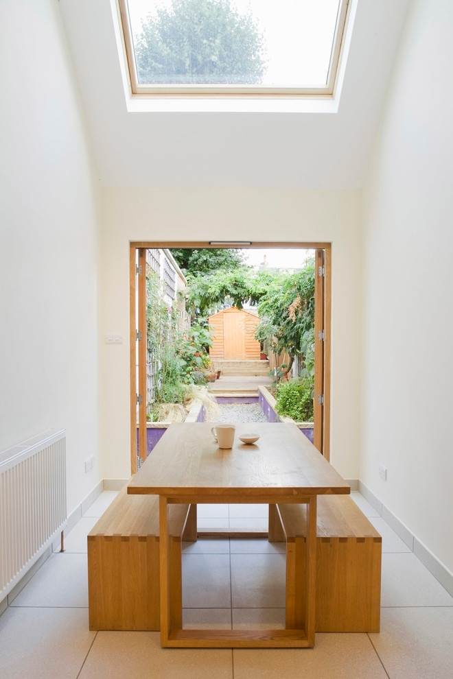 narrow dining room with white floor, white painted wall, glass roof, open garden on one side, a square table with two benches
