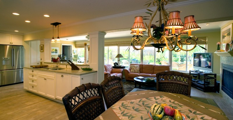open room of living room, kitchen, and dining room with rattan chairs, wooden table with leaves patterned table cloth