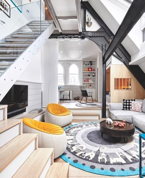 open space with indented living room with wooden floor, grey sofa, orange round sofa, blue grey rug, wooden round coffee table, TV, staircase, dining area