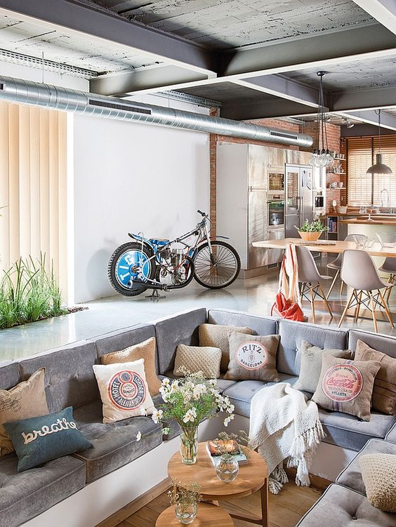 open space with kitchen area, dining area wth wooden table and grey midcentury chairs, grey sofa in indented floor in the middle