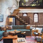 Open Space With Living Area With Green Velvet Corner Sofa, Wooden Chair With Grey Sofa, Round Coffee Table With Wooden Top, Garden With Glass Partition Garden Upstairs, Staircas
