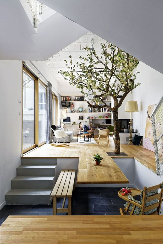 open space with living area with wooden floor, grey sofa, white rocking chairs, TV, floor lamp, kitchen area with wooden table from the continued wooden floor, wooden bench