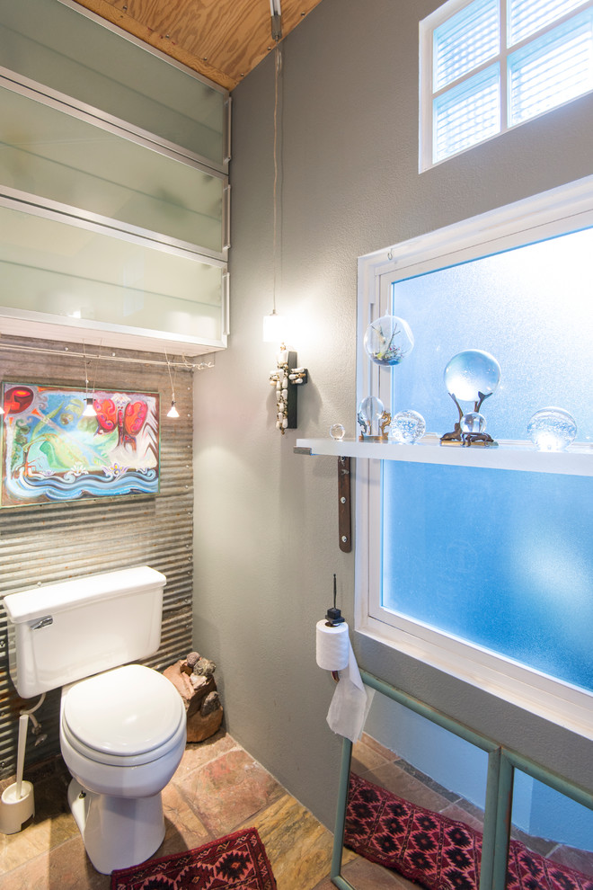 over the toilet storage accent wall frosted glass cabinet doors grey wall frosted glass window pendant lamp mirror wooden floor bathroom mat