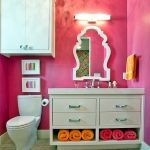 Over The Toilet Storage Pink Walls Vanity Undermount Sink White Framed Mirror Towel Holder White Wall Mounted Cabinet Brown Floor Tile Wall Sconce